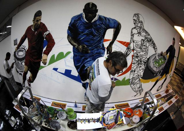 Brazilian artist Paulo Consentino works on a mural in celebration of the 2014 soccer World Cup at Congonhas airport in Sao Paulo May 25, 2014. Picture taken using fisheye lens. REUTERS/Paulo Whitaker (BRAZIL - Tags: SPORT SOCCER WORLD CUP SOCIETY)