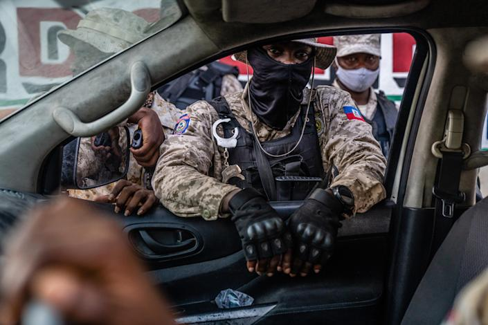 Haitian police speak with a driver near to a barricade in Port Au Prince, Haiti on Wednesday, July 14, 2021. (Federico Rios/The New York Times)
