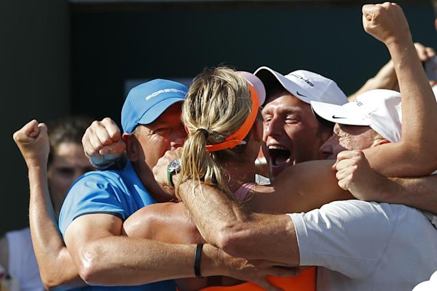 Russia's Maria Sharapova, center, celebrates with her coaches after winning the final of the French Open tennis tournament against Romania's Simona Halep at the Roland Garros stadium, in Paris, France, Saturday, June 7, 2014. Sharapova won in three sets 6-4, 6-7, 6-4. (AP Photo/Darko Vojinovic)