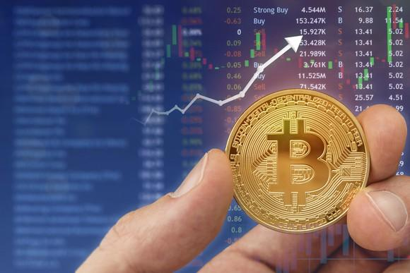 Person holding coin with stock chart in the background.
