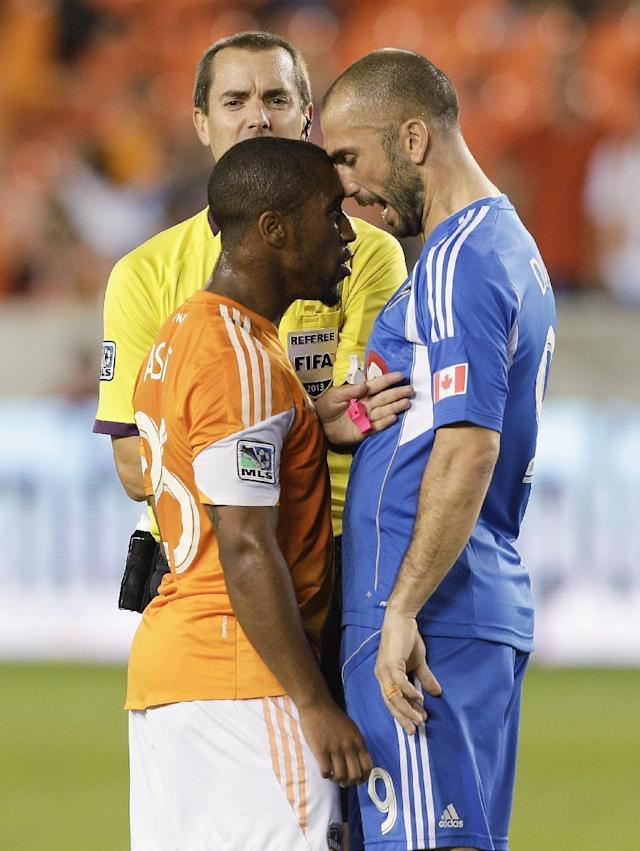 Houston Dynamo midfielder Corey Ashe (26) has words with Montreal Impact forward Marco Di Vaio (9) after a hard foul in the first half as referee Mark Geiger steps in during a knockout-round match in the MLS Cup soccer playoffs, Thursday, Oct. 31, 2013, in Houston. (AP Photo/Bob Levey)