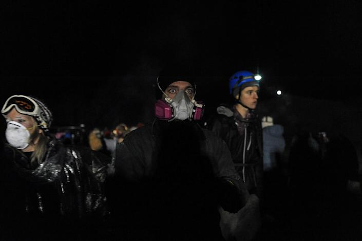 <p>A protester watches the confrontation with police from the sidelines during a protest against plans to pass the Dakota Access pipeline near the Standing Rock Indian Reservation, near Cannon Ball, N.D., on Nov. 20, 2016. (Stephanie Keith/Reuters) </p>