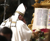 Pope Francis crosses himself in front of a statue of Baby Jesus after celebrating Mass on Christmas eve, at St. Peter's basilica at the Vatican, Thursday, Dec. 24, 2020. (Vincenzo Pinto/Pool Photo via AP)