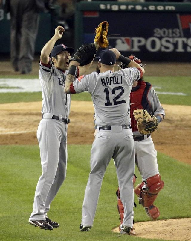 Boston Red Sox relief pitcher Koji Uehara, left, celebrates with Mike Napoli and Jarrod Saltalamacchia after the Red Sox defeated the Detroit Tigers 1-0 in Game 3 of the American League baseball championship series Tuesday, Oct. 15, 2013, in Detroit. (AP Photo/Charlie Riedel)