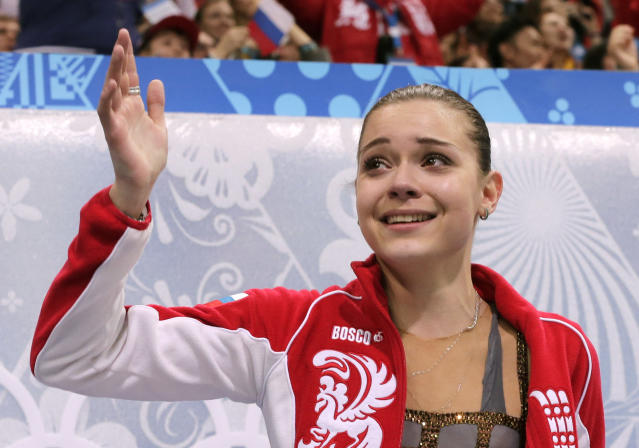 Adelina Sotnikova of Russia waves to spectators as she waits in the results area after completing her routine in the women's free skate figure skating finals at the Iceberg Skating Palace during the 2014 Winter Olympics, Thursday, Feb. 20, 2014, in Sochi, Russia. (AP Photo/Bernat Armangue)