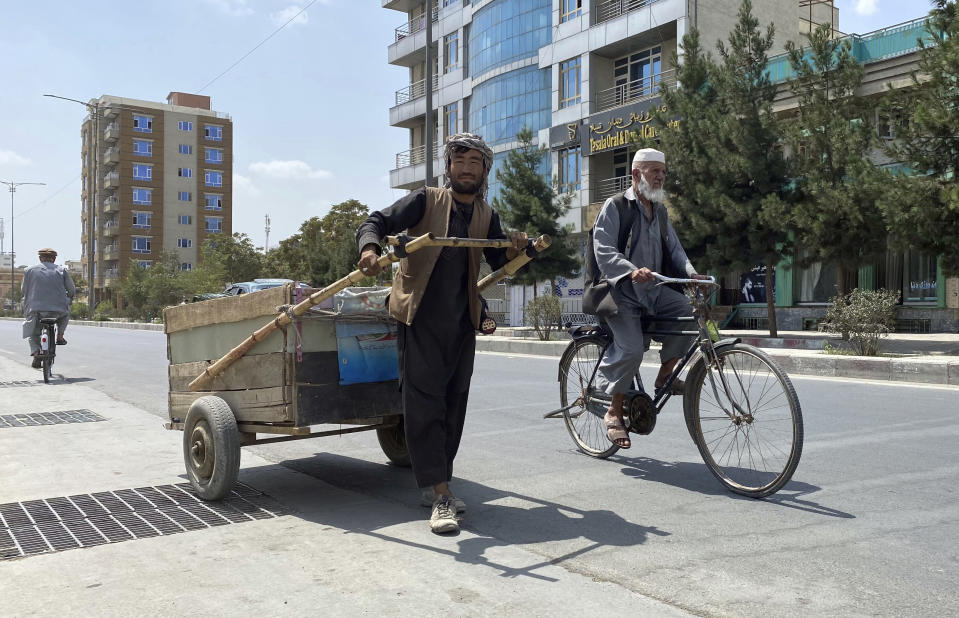 Sal Mohammad, 25, an Afghan man who gathers pieces of iron from the street to sell for scrap, pushes his handcart in Kabul, Afghanistan, Tuesday, Aug. 31, 2021. (AP Photo/Sayed Ziarmal Hashemi)