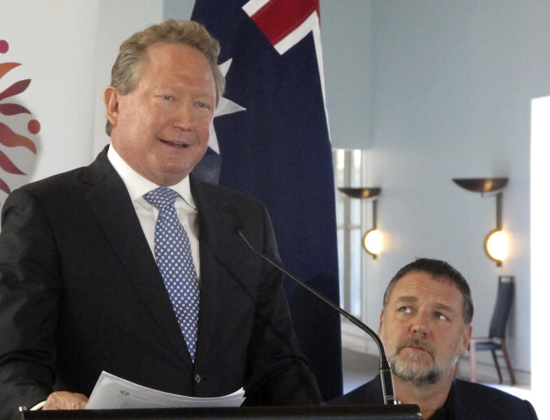 Iron ore mining magnate Andrew Forrest, left, gives a speech at Australia's Parliament House in Canberra, Australia, Monday, May 22, 2017, as actor Russell Crowe looks on. Crowe was master of ceremonies at the event. Forrest is donating 400 million Australian dollars ($300 million) to charities in what has been described as a new record in Australian philanthropy. The 55-year-old chairman of Fortescue Metal Group and his wife, Nicola, announced Monday the money will be spent on cancer research, Australian university research, supporting disadvantaged people including Aborigines, and fighting slavery around the world. (AP Photo/Rod McGuirk)