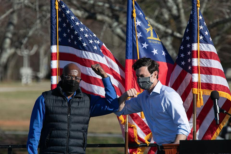CONYERS, GA - DECEMBER 05: Democratic U.S. Senate candidates Raphael Warnock (L) and Jon Ossoff bump elbows during an outdoor drive-in rally on December 5, 2020 in Conyers, Georgia. Ossoff and Warnock face Republican candidates Sen. David Purdue (R-GA) and Sen. Kelly Loeffler in a runoff election that will take place January 5th.  (Photo by Jessica McGowan/Getty Images)