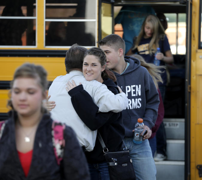 A high school student gets a hug from a teacher from West, Texas, as students arrive for classes at a temporary facility provided by the Connally Independent School District Monday, April 22, 2013, in Waco, Texas. West students returned back to class today after a massive explosion at the West Fertilizer Co. five days ago damaged three of West's four schools, killed 14 people and injured more than 160 others. (AP Photo/Charlie Riedel)