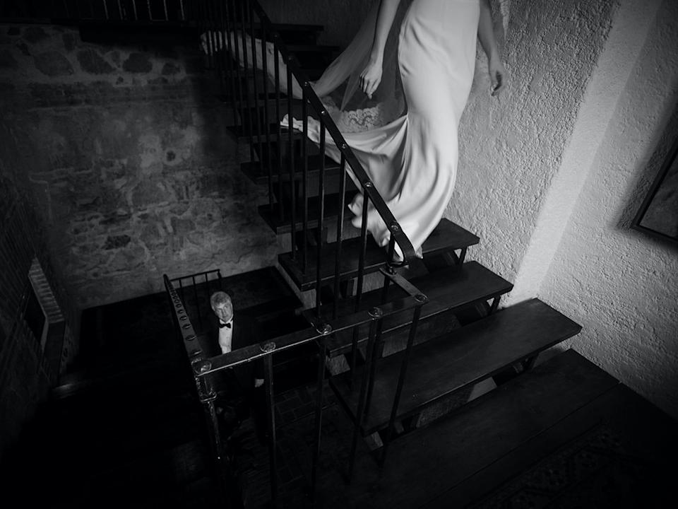 The lower half of a bride's body is visible walking down a set of stairs as her father looks up at her from a lower floor.