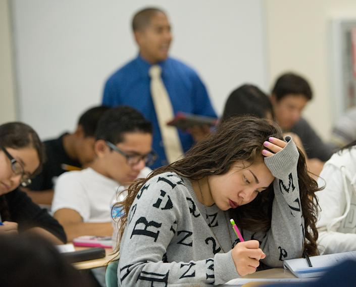 SANTA ANA, CA - SEPTEMBER 09: Jasmin Canada, 17, a senior at Godinez Fundamental High School in Santa Ana, works a math problem while teacher John Ninofranco, in back, instructs her AP Calculus class.    ///ADDITIONAL INFORMATION:   Ð MINDY SCHAUER, ORANGE COUNTY REGISTER Ð  shot 090914  ap.santaana.0910  Santa Ana schools are trying to increase scores and performance in Advanced Placement classes by teaming with The College Board. Godinez High School teacher John Ninofranco teaches his  AP Calculus class. (Photo by Mindy Schauer/Digital First Media/Orange County Register via Getty Images)