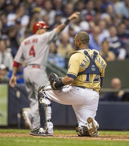Milwaukee Brewers' Martin Maldonado gets up after St. Louis Cardinals' Yadier Molina, rear, scored during the third inning of a baseball game Thursday, May 2, 2013, in Milwaukee. The Cardinals scored three times on plays at the plate in the inning. (AP Photo/Tom Lynn)