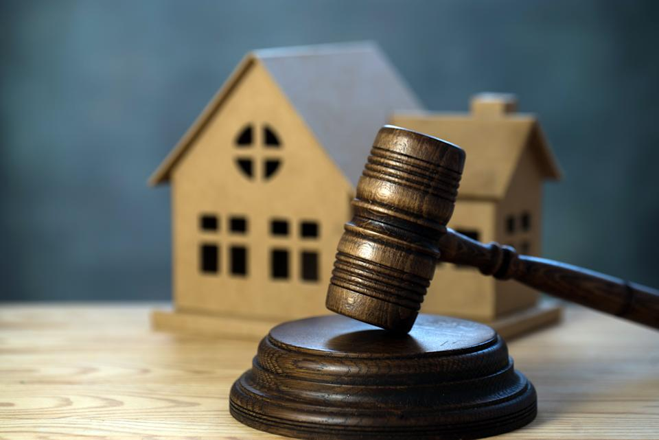 House auctions. A wooden hammer and a paper house