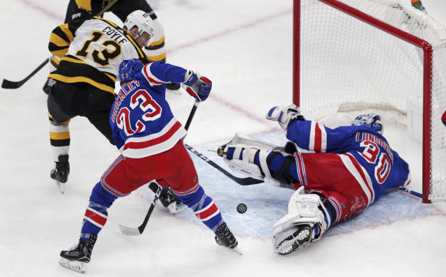 New York Rangers goaltender Henrik Lundqvist (30) sprawls on the ice as he makes a save on a shot by Boston Bruins center Charlie Coyle (13) during the first period of an NHL hockey game in Boston, Wednesday, March 27, 2019. At center is Rangers left wing Connor Brickley (23). (AP Photo/Charles Krupa)
