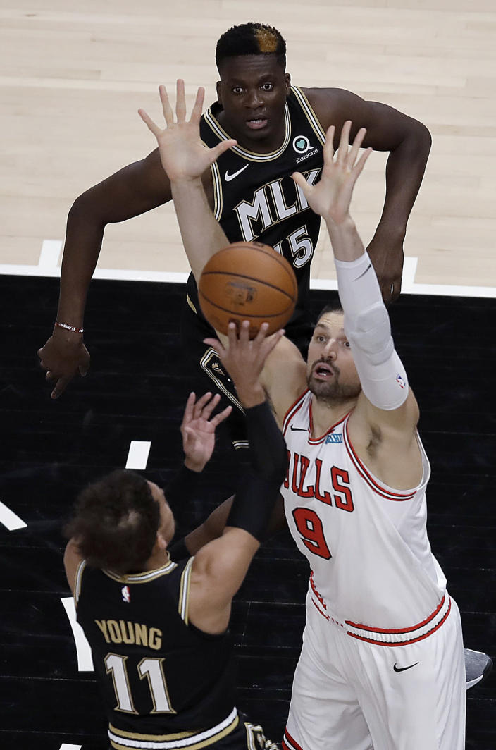 Chicago Bulls' Nikola Vucevic (9) defends against the shot of Atlanta Hawks' Trae Young (11) during the first half of an NBA basketball game Friday, April 9, 2021, in Atlanta. (AP Photo/Ben Margot)