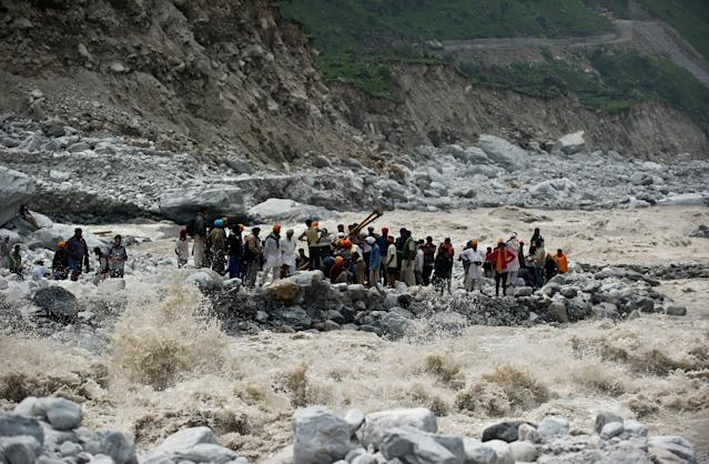 Stranded Indian pilgrims wait to be rescued on the side of a river at Govind Ghat on June 23, 2013. Rescue operations have intensified in northern India where up to 1,000 people are feared to have died in landslides and flash floods that have also left pilgrims and tourists stranded without food or water for days. AFP PHOTO/MANAN VATSYAYANA