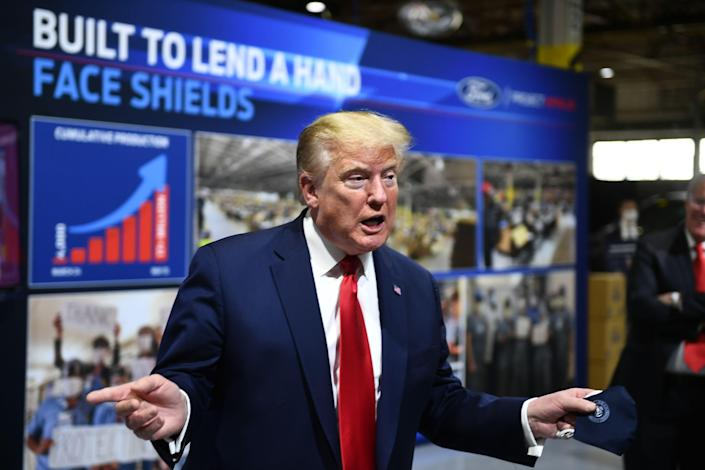 US President Donald Trump holds a mask as he speaks during a tour of the Ford Rawsonville Plant in Ypsilanti, Michigan on May 21, 2020.