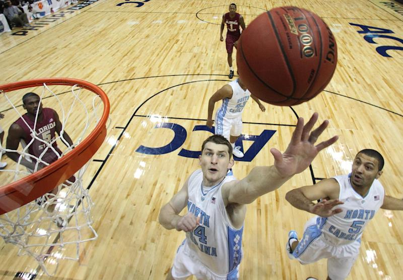 North Carolina forward Tyler Zeller (44) works to recover a rebound as North Carolina guard Kendall Marshall (5) and Florida State forward Bernard James (5) watch during the first half of an NCAA college basketball game in the final of the Atlantic Coast Conference tournament, Sunday, March 11, 2012, in Atlanta. (AP Photo/Chuck Burton)