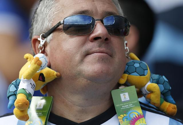 An Argentine supporter has stuffed-toy World Cup mascots attached to his sunglasses before the group F World Cup soccer match between Nigeria and Argentina at the Estadio Beira-Rio in Porto Alegre, Brazil, Wednesday, June 25, 2014. (AP Photo/Jon Super)