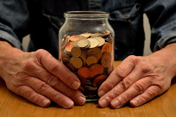 A persons hands are seen holding a money savings jar full of coins...