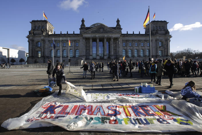 A woman works on a giant poster reading 'Climate Strike' during the 'Youth For Climate' strike protest in front of the Reichstag building in Berlin, Friday, Jan. 18, 2019. (AP Photo/Markus Schreiber)