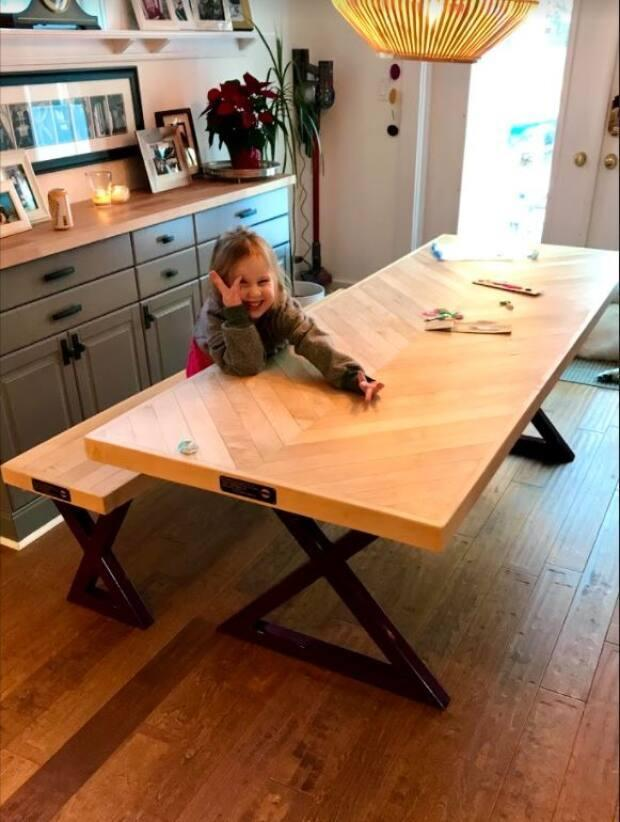 The Armhein's young daughter sits at the table made from the original floors from the Hartley House.