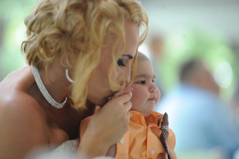 Newlywed Christine Stevenson kisses the hand of her son, Logan Stevenson, 2, after marrying Sean Stevenson in a wedding ceremony on Saturday, Aug. 3, 2013 in Jeannette, Pa. Logan stood with his grandmother, Debbie Stevenson, during a 12-minute ceremony uniting Logan's mother and his father. The boy has leukemia and other complications. The Stevensons abandoned an original wedding date of July 2014 after learning from doctors late last month that their son had two to three weeks to live. The couple wanted Logan to see them marry and to be part of family photos. Logan, who was born Oct. 22, 2010, was diagnosed shortly after his first birthday with acute myeloid leukemia. He has Fanconi anemia, a rare disease that often leads to cancer. (AP Photo/Tribune Review, Eric Schmadel) PITTSBURGH OUT