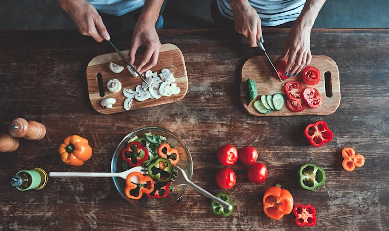 Cropped image of romantic couple is cooking on kitchen. Handsome man and attractive young woman are having fun together while making salad. Healthy lifestyle concept.