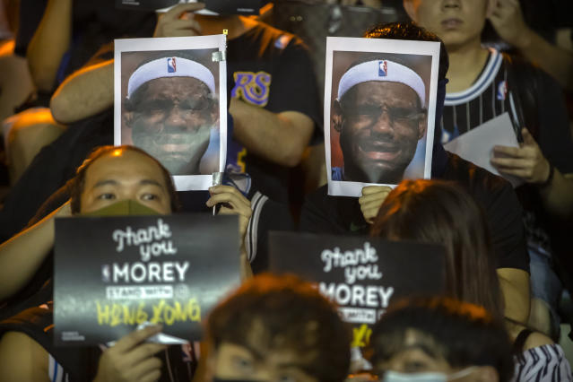 Demonstrators hold up photos of LeBron James grimacing during a rally at the Southorn Playground in Hong Kong on Tuesday. (AP Photo/Mark Schiefelbein)