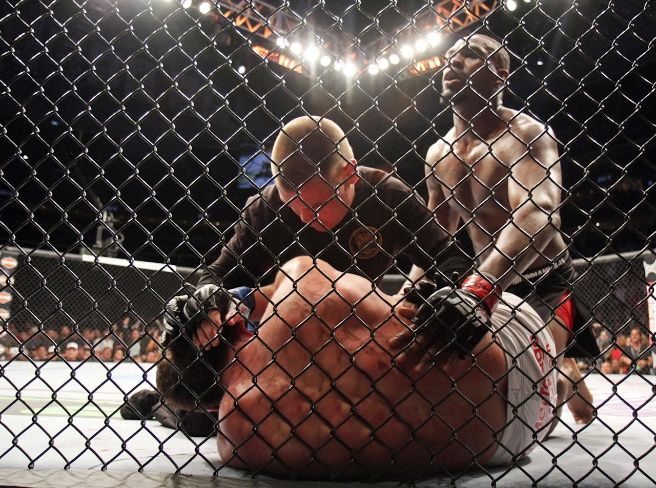 The referee stops the fight as Jon Jones defeats Chael Sonnen in their UFC 159 Mixed Martial Arts light heavyweight title bout in Newark, N.J., Saturday, April 27,2013. Jones retained his title via first round TKO. (AP Photo/Gregory Payan)