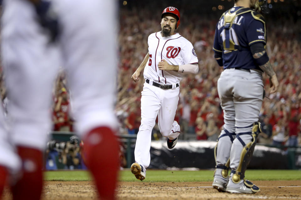 Washington Nationals' Anthony Rendon comes across the plate as Washington Nationals' Juan Soto drives in three runs with a single in the eighth inning to put the Washington Nationals up over the Milwaukee Brewers in a National League wild-card baseball game at Nationals Park, Tuesday, Oct. 1, 2019, in Washington. The Nationals won 4-3. (AP Photo/Andrew Harnik)