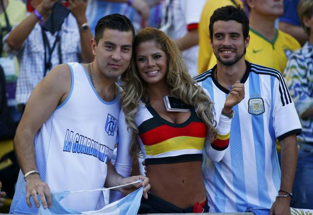 A fan of Germany poses with fans of Argentina as they wait for the start of their 2014 World Cup final at the Maracana stadium in Rio de Janeiro July 13, 2014. REUTERS/Michael Dalder (BRAZIL - Tags: SOCCER SPORT WORLD CUP)