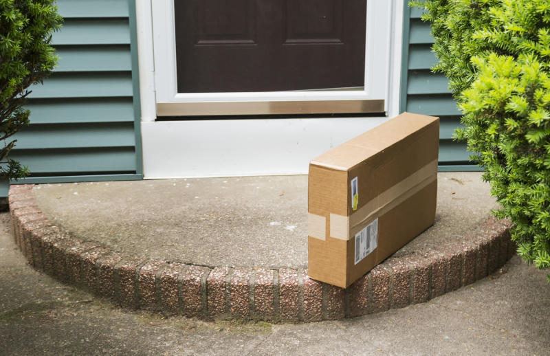 A brown cardboard box is left on the front stoop after being delivered while no one was home.