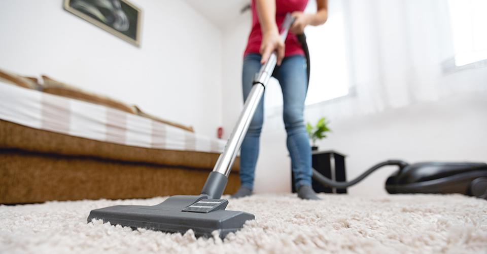 Woman vacuum cleaning her room