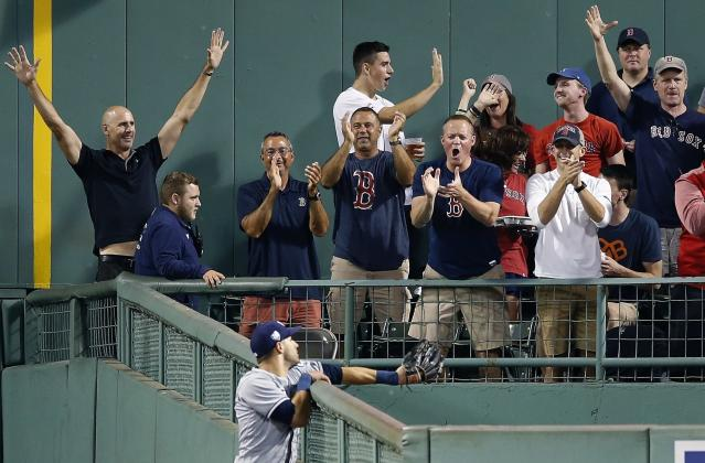 Fans celebrate the solo home run by Boston Red Sox's J.D. Martinez as Tampa Bay Rays' Kevin Kiermaier looks after the ball in the bullpen during the third inning of a baseball game in Boston, Saturday, Aug. 18, 2018. (AP Photo/Michael Dwyer)