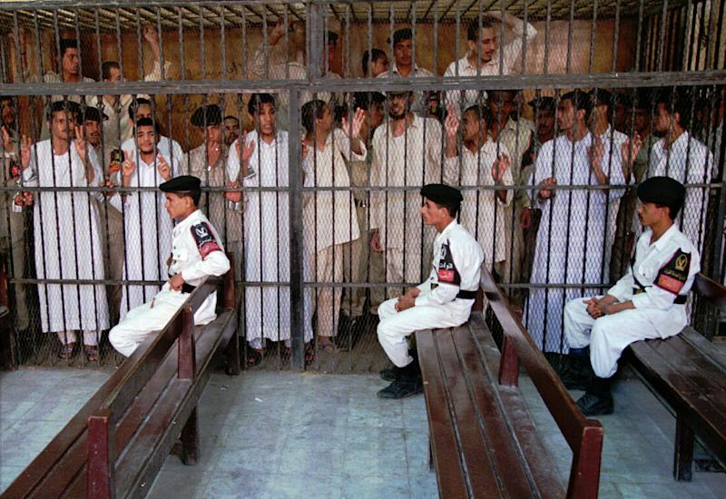 FILE - In this Oct. 31, 1996 file photo, Islamic militants await their verdict as Egyptian policemen sit on guard in a court in Cairo. The court sentenced three of the men to 25 years in prison for taking part in attacks that left 63 people dead in violence between Muslim militants and police. The trial, which lasted a year, also earlier sentenced two men still at large to death in the case on charges of assassinating a security chief, several aides and five civilians in southern Egypt in 1993. It was one of the most perplexing events of Egypt's 2011 revolution: Attacks on prisons that broke out more than 20,000 inmates, among them Hamas and Hezbollah militants and Muslim Brotherhood leaders, including the man who is now the country's president, Mohammed Morsi. Now a court case is trying to uncover for the first time who was behind the attacks, raising political headaches for Morsi. (AP Photo/Enric Marti, File)