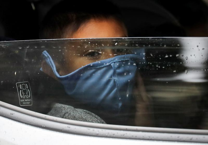 A boy wears a face mask as food is delivered to his family's truck at a food bank distribution center in Van Nuys, California, in April. At the time, organizers said they had distributed food for 1,500 families during the COVID-19 pandemic. (Mario Tama via Getty Images)
