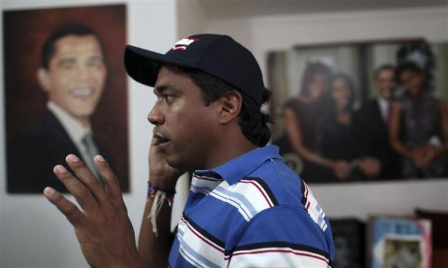 Colombian attorney Silvio Carrasquilla takes a call while surrounded by the Barack Obama memorabilia collection he uses to adorn his home in Turbaco, near Cartagena, April 11, 2012.