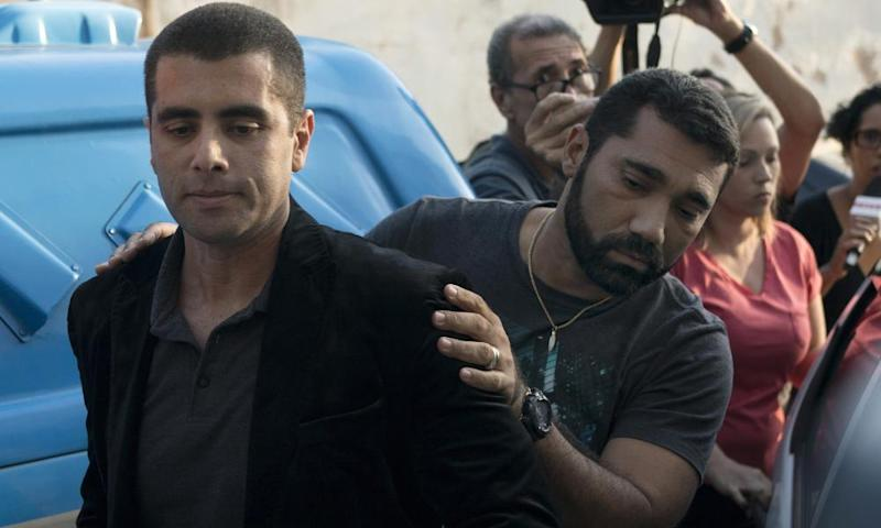 The celebrity plastic surgeon Denis Furtado is escorted by police after his arrest in Rio de Janeiro, Brazil on Thursday.