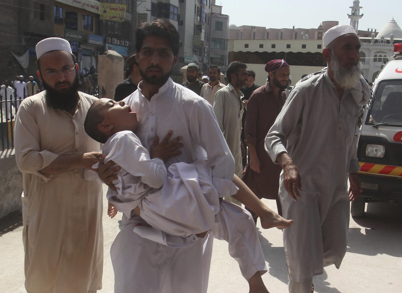 Family member rush a boy to a hospital after receiving a polio vaccination, in Peshawar, Pakistan, Monday, April 22, 2019. Pakistani officials say hundreds of school children have been taken to hospitals complaining of nausea and vomiting after being given polio vaccinations. (AP Photo/Muhammad Sajjad)