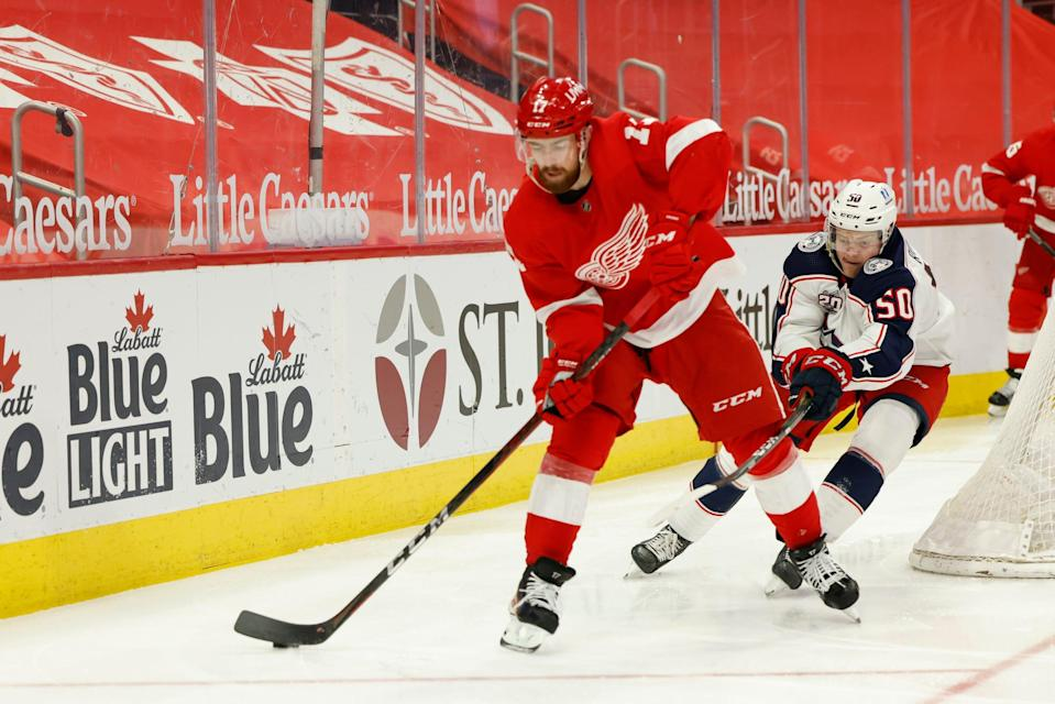 Detroit Red Wings defenseman Filip Hronek (17) skates with the puck chased by Columbus Blue Jackets left wing Eric Robinson (50) in the third period  March 27, 2021, at Little Caesars Arena.