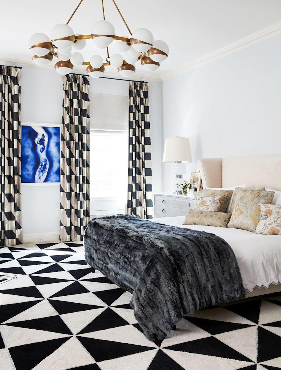 "<p>Bold, over-the-top black and white carpeting and drapes blend nicely with the glam light fixture, eye-catching artwork, and luxe throw blanket while the delicate pinks and creams on the bed soften up this bedroom by <a href=""https://www.fawngalli.com/"" rel=""nofollow noopener"" target=""_blank"" data-ylk=""slk:Fawn Galli"" class=""link rapid-noclick-resp"">Fawn Galli</a>. </p>"