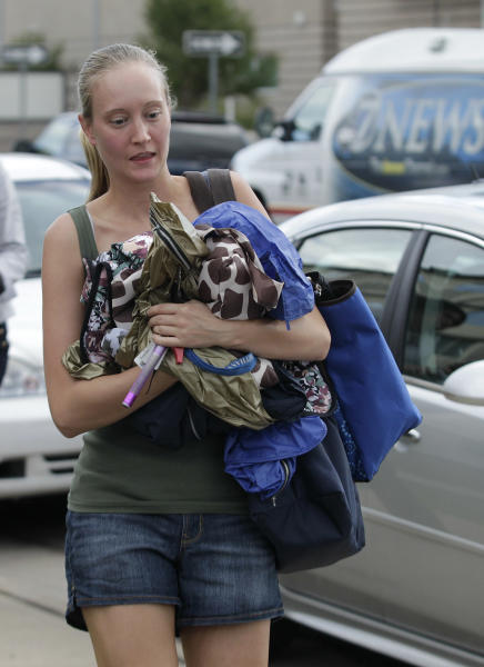 An unidentified resident of the apartment building where suspected Aurora movie theater gunman James Holmes lived, carries items to her apartment, Wednesday, July 25, 2012, after residents were allowed back in the building, which had been closed off by police due to the continuing investigation of the shooting. (AP Photo/Ted S. Warren)