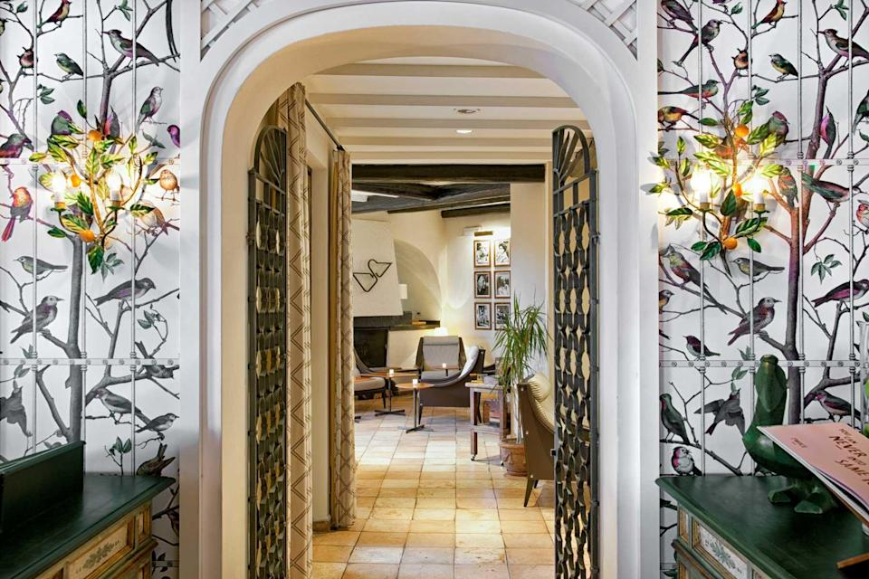 Interior space with bird wallpaper at the Hotel Il Pellicano, voted one of the best hotels in the world