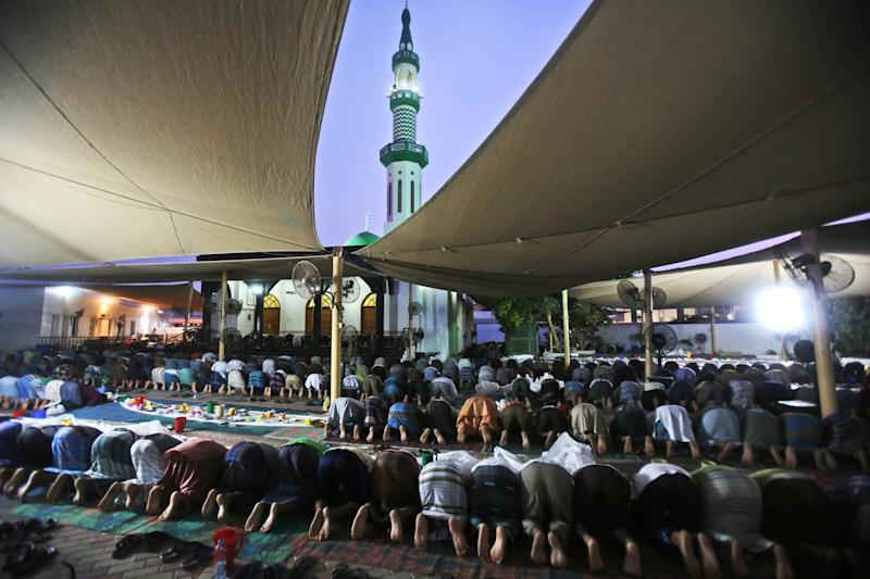 In this Sunday, July 28, 2013 photo, Muslim labor workers pray after breaking their fast during the holy month of Ramadan in Dubai, United Arab Emirates. Across Muslim world, families gather at sunset after the daylong fast during the holy month of Ramadan. In a parking lot in Dubai, a group of Muslim laborers from India separated from their homeland like millions of other workers across the Gulf join for a game of cricket and to swap stories late into the evening. (AP Photo/Kamran Jebreili)