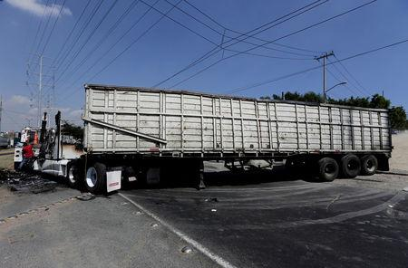 The wreckage of a tractor-trailer set ablaze by members of a drug cartel is seen blocking a road in Guadalajara May 1, 2015.REUTERS/Alejandro Acosta/File Photo