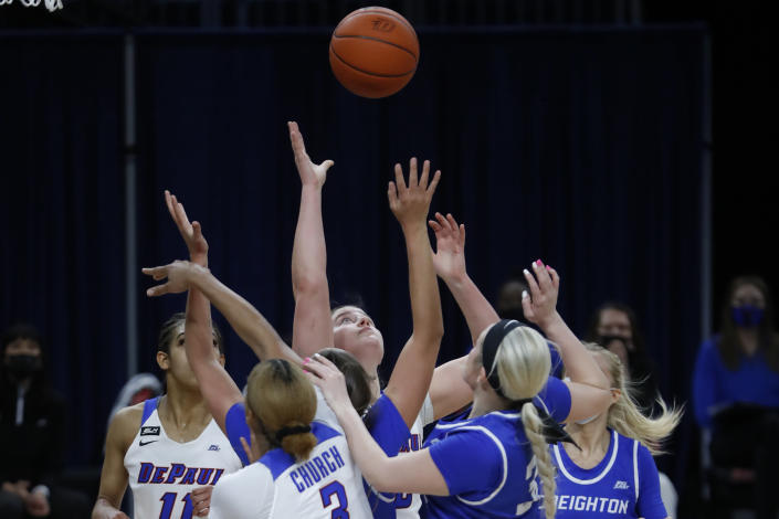 DePaul forward Jorie Allen, center, reaches for a loose ball during the first half of an NCAA college basketball game against Creighton, Saturday, Feb. 20, 2021, in Chicago. (AP Photo/Shafkat Anowar)