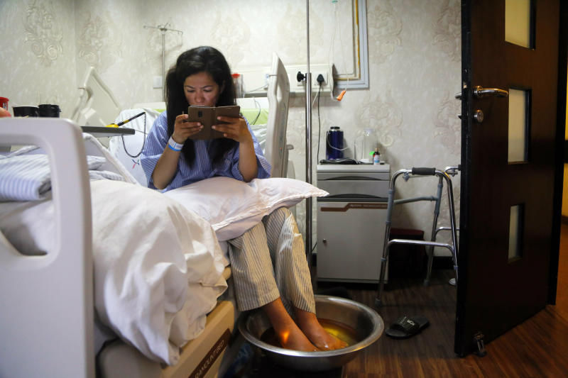 Indian climber Ameesha Chauhan who survived dangerous overcrowding on Mount Everest checks her cell phone as she gets treatment at a hospital after she was rescued in Kathmandu, Nepal, Tuesday, May 28, 2019. Seasoned mountaineers say the Nepal government's failure to limit the number of climbers on Mount Everest has resulted in dangerous overcrowding and a greater number of deaths. (AP Photo/Niranjan Shrestha)