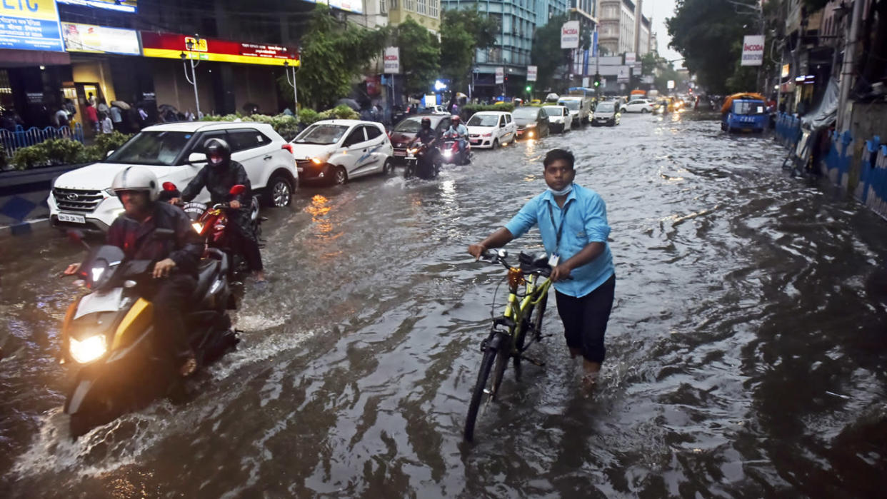A man wades through a flooded street with his bicycle after a heavy rainfall in Kolkata, India, in July.
