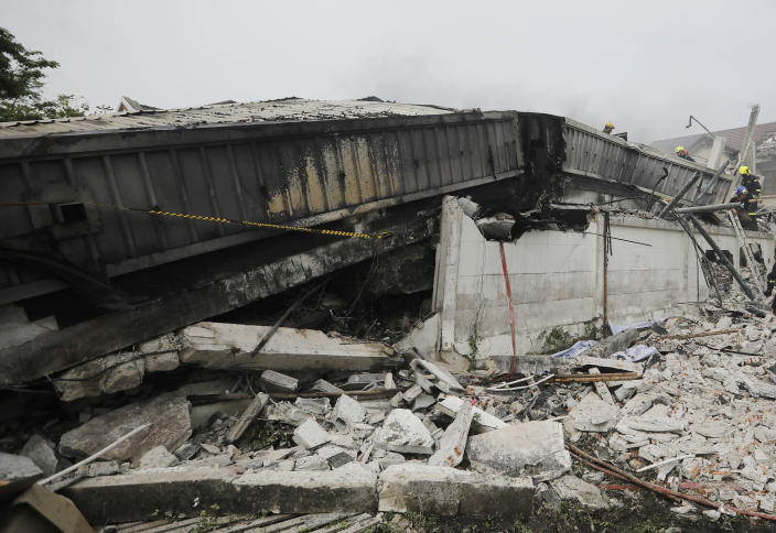Rescue teams search for possible victims trapped in a house that collapsed in Bangkok, Thailand, Saturday, April 3, 2021. A number of people were killed after a three-story house in Bangkok collapsed on Saturday due to fire, the city government said. (AP Photo/Str)